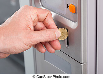 Human hand inserting coin in vending machine - Close-up of...