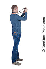 Back view of man photographing photographer in jeans Rear...