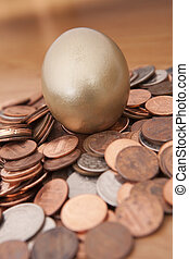 golden nest egg - Golden egg nested on pile of coins