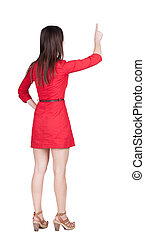 Back view of young brunette woman pointing at wall.