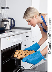 Woman Placing Cookies In Oven - Young Woman Placing Tray...