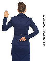 Business woman holding crossed fingers behind back while...