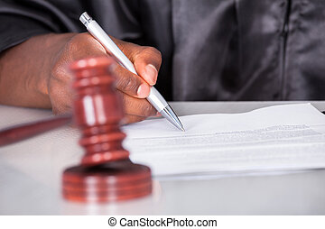 Male Judge Writing On Paper In Courtroom - Close-up Of A...