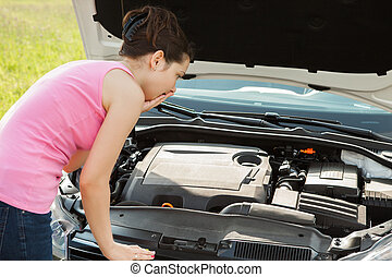 Woman Looking Under Hood Car - Shocked Young Woman Looking...