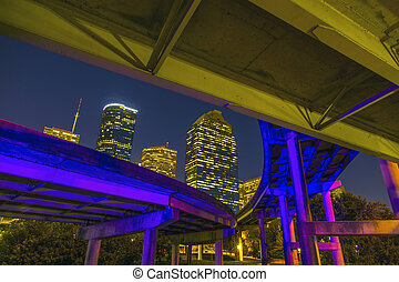 View on downtown Houston by night with bridges in colorful...