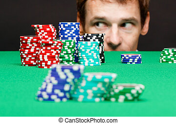 man looking under the table on playing chips