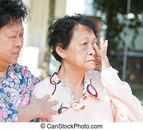 Sadness senior woman wiping off her tears in eyes, consoling...
