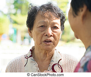 Sadness senior woman telling sad story to her friend, with...