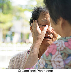Consoling crying old mother - Candid shot of a mature woman...