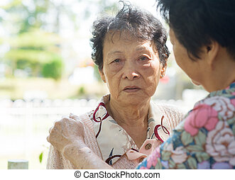 Mature woman consoling her crying old mother - Candid shot...