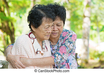 Asian mature woman hugs and consoling her crying old mother...
