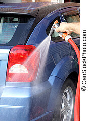 Washing car - Hand holding hose with spray gun washing car