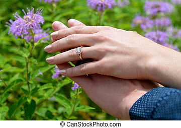 Couples hands showing ring - Young woman's hand resting on...