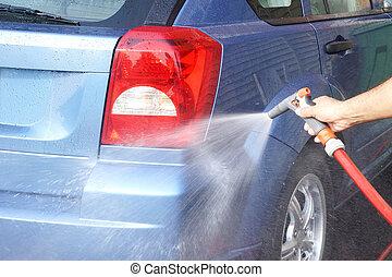 Washing car - Hand holding water hose with spray gun washing...