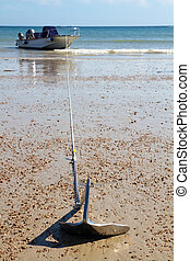 Motorboat on anchor at a sandy beach