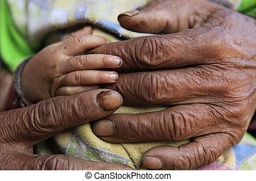 Caring  - Old hand and young hand holding.