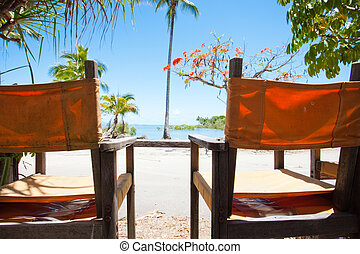 Two deck chairs overlooking a tropical beach - Two...