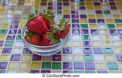 Fresh Strawberries in Clear Bowl on Purple, Yellow and Green...