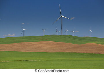 White Wind Turbines Over Rolling Green Hills