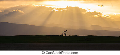 Pumpjack with Crepuscular Rays and Rocky Mountains