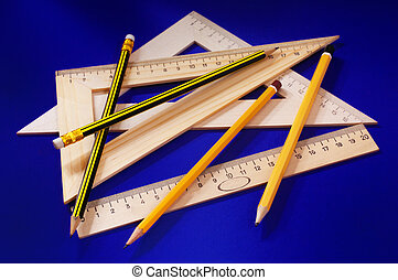 Measuring devices and a pencil on a dark blue background