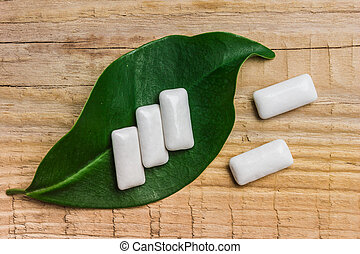 chewing gum is on a leaf on the background of wooden boards