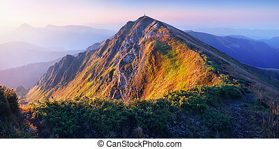 Sunrise in the mountains - Rising sun lights up a mountain...