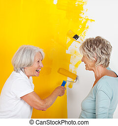 Senior Women Painting Wall With Yellow Paint - Side view of...