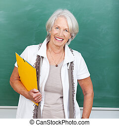 Senior Woman Holding File Against Chalkboard - Portrait of...