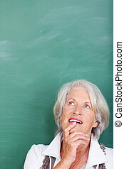 Senior woman standing thinking against a green blackboard...