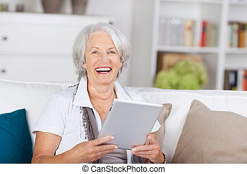 Laughing beautiful senior with a tablet-pc - Laughing...