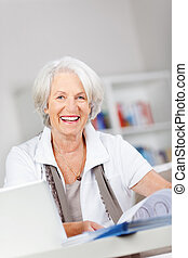 Senior lady working in a home office - Attractive smiling...