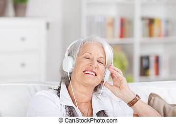 Modern senior woman listening to music on a set of...
