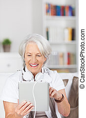 Senior Woman Using Digital Tablet In House - Happy senior...