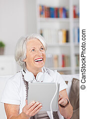 Modern senior woman with headphones and a tablet