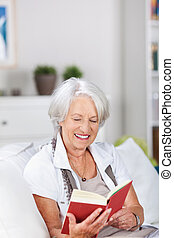 Elderly woman relaxing and reading a book