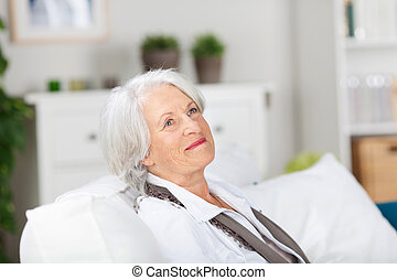 Daydreaming smiling elderly woman relaxing on a sofa in her...