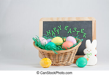Chalkboard With Happy Easter Words and Basket of...