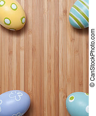 Hand Painted Easter Eggs in Pastel Colors on Wooden Cutting...