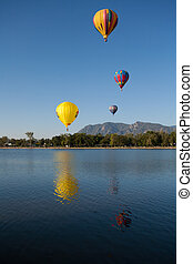 Colorful Hot Air Balloons Flying Over a Lake with Rocky Mountains and Clear Blue Skies