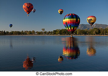 Colorful Hot Air Balloons Reflected in a Lake with Rocky...