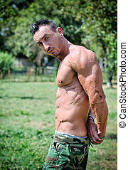 Muscle man doing triceps pose outdoors in a park