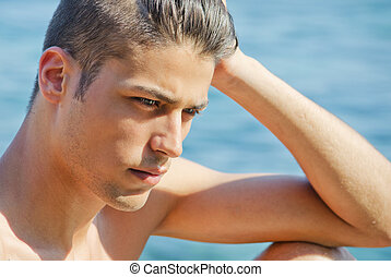 Handsome young man thinking next to the sea