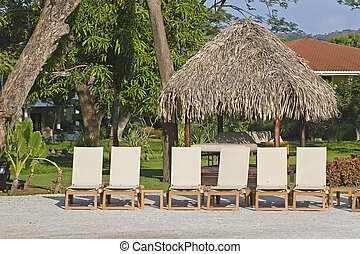 Chaise Lounges and Straw Hut - White lounge chairs and a...