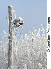 Cracked old style wooden street light covered with hoar frost in winter
