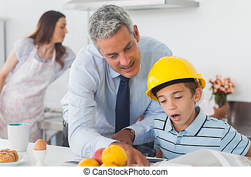 Father showing son his blueprints as he is wearing hardhat...