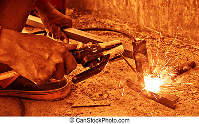 worker welding two pieces of metal together - Closeup view...