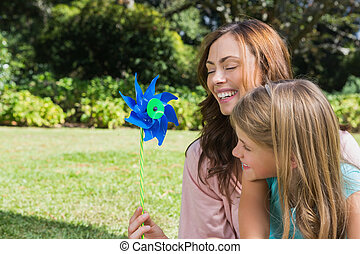 Mother with daughter with a pinwheel in the park on a sunny...