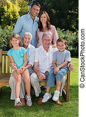 Happy multi generation family sitting in the park on a bench...