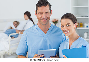 Portrait of surgeons in bright surgery with doctor attending patient on background